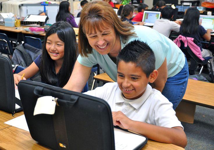 Professeur aidant un élève devant son ordinateur