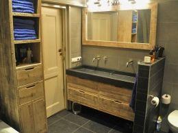 Sfeervolle badkamer van oud steigerhout, hier mooi gecombineerd met grijze en zwarte steen. Het zwevende wastafelmeubel b140xd50xh50cm heeft 4 grote lades, lopend op geleiders met handige en elegante handgrepen. Bijpassend een lijst b140xh70cm en 9cm breed incl. spiegel. En dan nog de zwevende kast met o.a. 2 lades en een deurtje b40xd40xh180cm. De meubels zijn apart te bestellen en kunnen op maat worden gemaakt. Wasbak, kranen, verlichting e.d. zijn privébezit. Deze set is te bestellen…