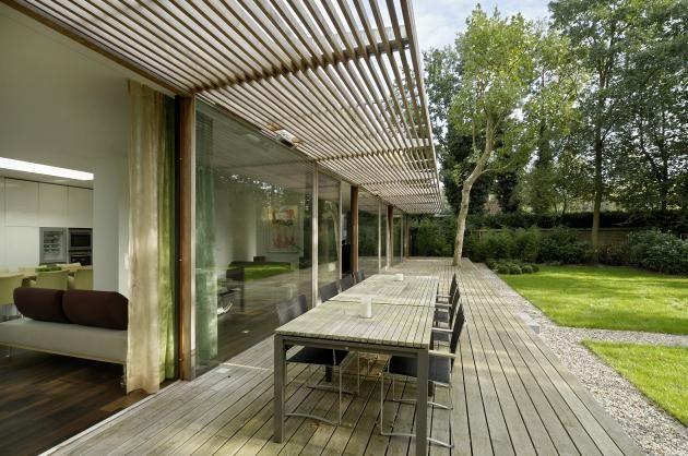 een houten terras en luifel tegen het huis