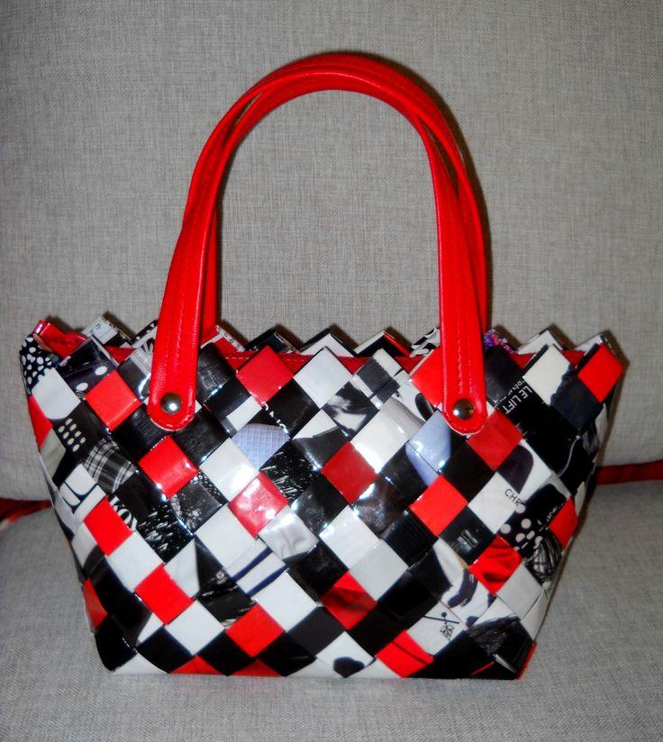 Τσάντα από πλαστικοποιημένο περιοδικό σε λευκό,μαύρο και κόκκινο.Με κόκκινα λουράκια χειρός και κόκκινο φερμουάρ. Διαστάσεις: 31 εκ.(μήκος) Χ 18 εκ.(ύψος) Χ 13 εκ. (πάτος).
