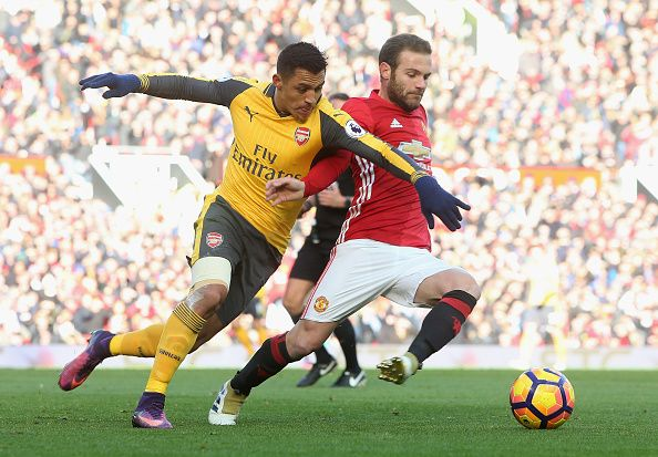 Juan Mata of Manchester United in action with Alexis Sanchez of Arsenal during the Premier League match between Manchester United and Arsenal at Old...