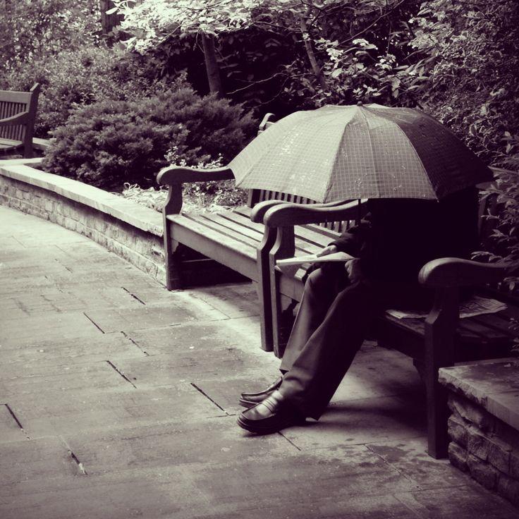 Man under umbrella contemplating his paper - Finsbury Circus, Lpndon in 2009