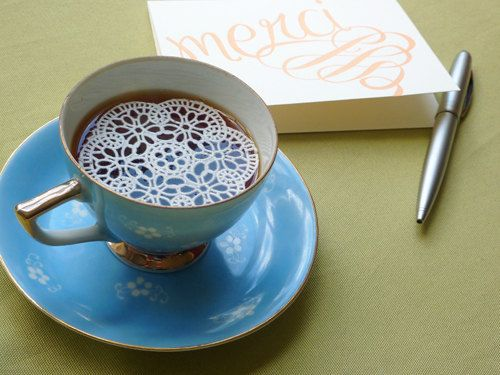 Edible sugar doilies add sweet whimsy to a simple cup of tea.