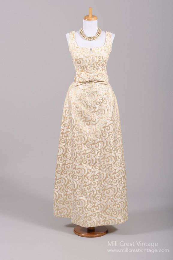 Designed in the 60's, this quintessential vintage wedding gown is done in a cream and metallic gold swirl patterned brocade over an acetate lining. The sleeveless bodice features a scooped neckline wi