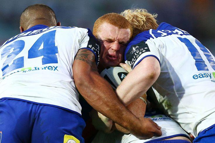 Alex McKinnon, dei Newcastle Knights, viene placcato da due avversari durante una partita contro i Canterbury Bulldogs della lega rugby a 13...