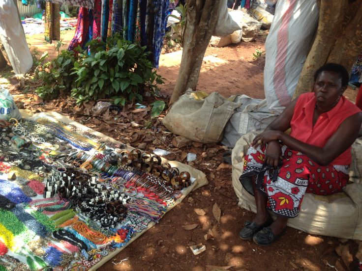 Nairobi Maasai Market: the Maasai sit around on rudimentary benches under protective parasols, busily hand-making a variety of objects, resting, chatting amongst themselves or trying to attract the attention of the tourists.