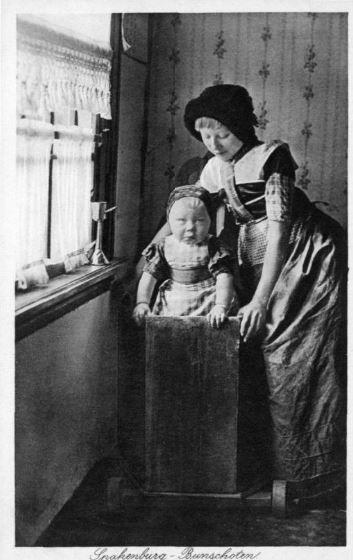 Afbeelding van een meisje en een kind in een kinderstoel in klederdracht in een een huis te Spakenburg (gemeente Bunschoten). 1913 Weenenk & Snel #Utrecht #Spakenburg