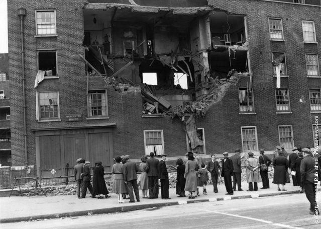 Inhabitants of Kennington Road in south-east London gather to survey the damage to a blitzed building after a World War II German air raid. 8th September 1940