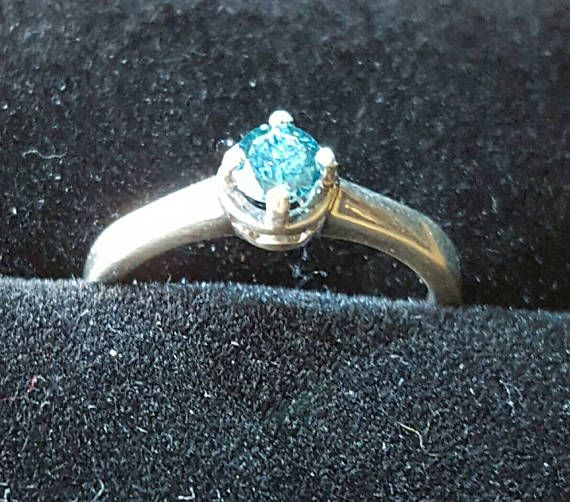This is a 4.4mm blue diamond in a sterling silver polished ring. The size is 6.5. The ring will be free shipped with a LED ring box for a magic experience. The diamond have a clarity of I2, its not a perfect diamond but you have to look it with magnifier glass to see it =) Return is accepted 7 days after the reception of the ring.  Voici une bague en argent sterling sertie dun diamant bleu de 4.4mm. Le diamant contient des impuretés visible à la loupe et est dune clarté de classe I2. La ...