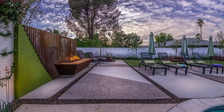 A large backyard patio features lounge chairs for relaxing and a rectangular fire pit for ambiance. Shade umbrellas are within easy reach for extra-sunny days.