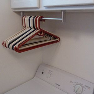 towel bar mounted under cabinet in laundry room for hangers