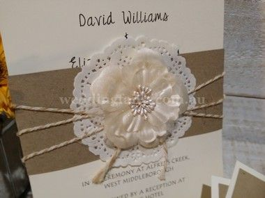 An A5 261gsm card, detailed corner, embossing and crimping.  Wrapped with natural recycled apper tied with Bakers Twine and finished with a doily and Camellia Flower.  Please allow 4 weeks from final artwork approval for package and posting.