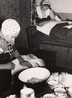 Streekdracht  Kraamvrouw en baker omstreeks 1935  Spakenburger dracht   Nog in de jaren dertig moest een vrouw in Spakenburg na de bevalling veertien dagen in bed blijven. Soms bleven de bedgordijnen de eerste week gesloten. Men was bang voor kraamvrouwenkoorts. Zij en de baby werden verzorgd door haar moeder of door een baker. Deze moeders hielden vaak oude gewoontes in stand. Het was moeilijk voor moderne vroedvrouwen en artsen daar verandering in te brengen.     Op de fotowordt de baby…