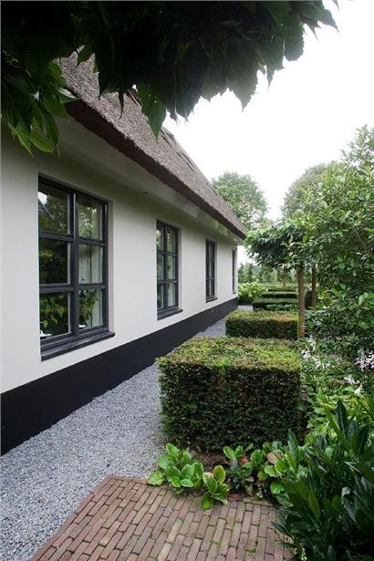 Mooi huis met tuin met oude bestrating, grijs grind en vierkante struiken en leibomen.