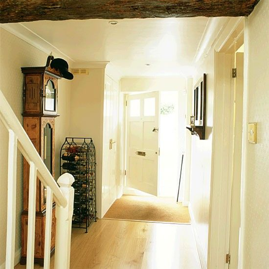 A neutral palette makes this hallway look clean, fresh and welcoming. Light pours in through the glazed panels in the wide front door, while the grandfather clock acts as an impromptu hat stand.