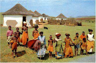 Xhosa-vroue en kinders voor hul tradisionele hutte in 'n klein Xhosa-nedersetting op die platteland