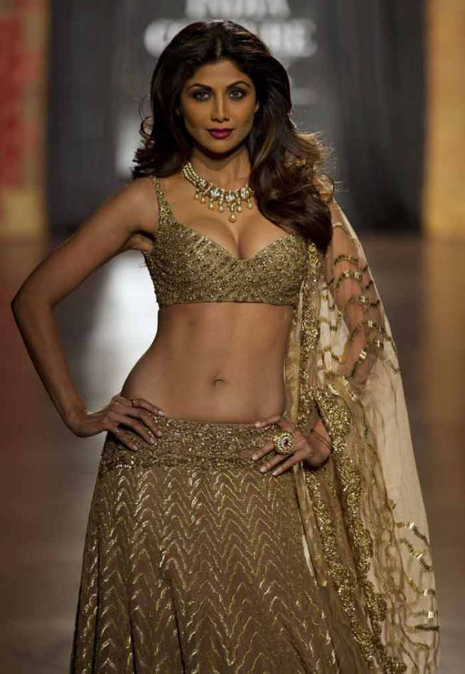 Shilpa Shetty in a heavily embroidered golden lehenga-choli as she walked the ramp at AICW 2015.
