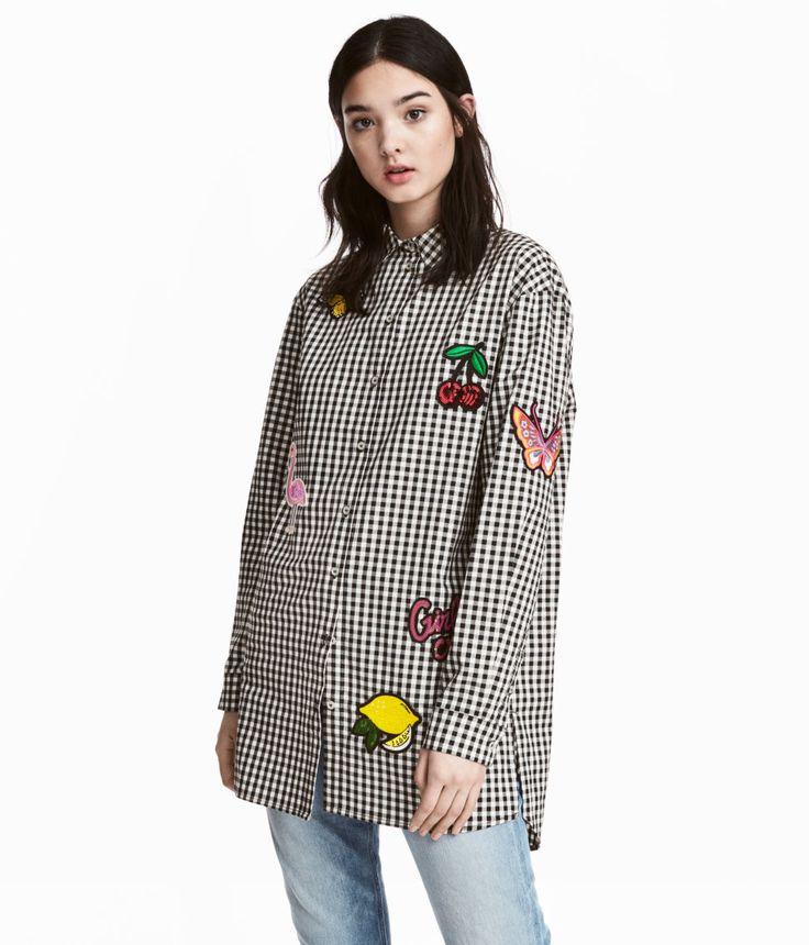 Svart/Vit rutig. En lång skjorta i rutig bomullskvalitet med broderade applikationer och paljetter. Skjortan har lång ärm med manschett och knäppning. Något