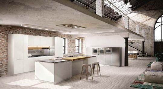 reforma cocina abierta en loft rehabilitado, isla con zona de cocción y barra, módulo con fregadero y armarios, mueble de acero inoxidable para electrodomésticos, suelo parquet