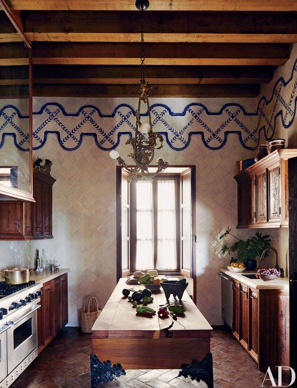 At their home in Mexico, designers Andrew Fisher and Jeffry Weisman devised the kitchen's frieze as well as the mesquite-and-sabino-wood island, whose bronze legs were sculpted by Fisher | archdigest.com