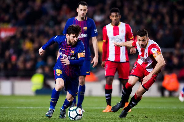 Lionel Messi of FC Barcelona runs with the ball next to Alex Granell of Girona FC during the La Liga match between Barcelona and Girona at Camp Nou on February 24, 2018 in Barcelona.