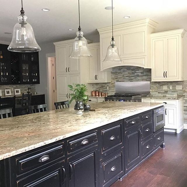 Farmhouse kitchen, two-tone kitchen, distressed cabinets, large kitchen island, black cabinets, glass pendants, stone backsplash | Farmhouse Redefined