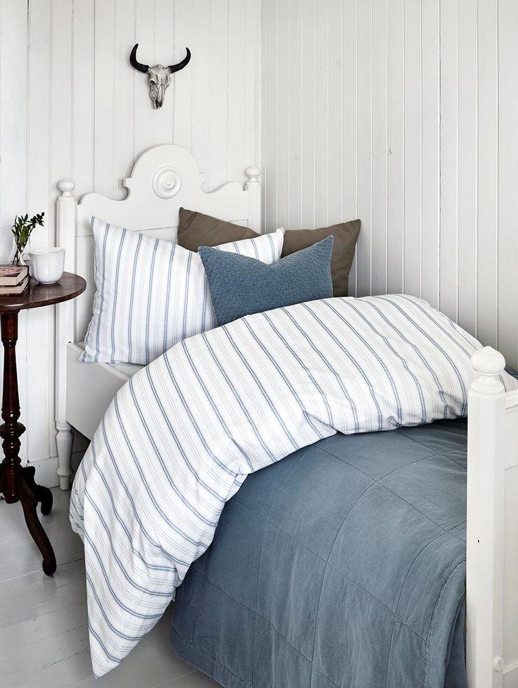 Stian sengesett i mørk marineblå striper mot hvit bunn.