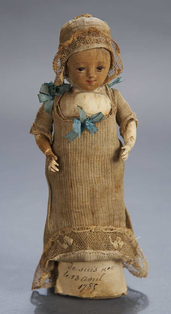 "The doll is wearing her original gown with lace trim and blue silk ribbons,and matching lace-edged cap.French,late-18th century,a hand-written paper under the gown reads ""Je suis née le 13 avril 1785"" (I was born April 13,1785)."