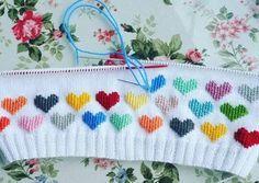 Corazones de colores bordados sobre chaleco tejido .