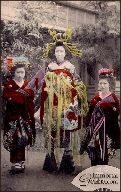 """The middle one is called a tayu, which is the highest rank of oiran/courtesan, these are cultered and refined prostitiues. Tayu are the only ones who wore those towering shoes. Next to her are kamuro, """"Child attendents"""" they were her apprentices."""