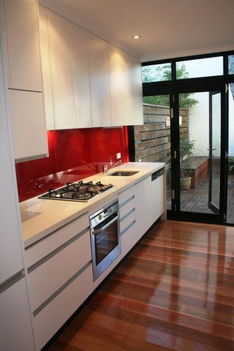 Modern white kitchen with red glass splashback, Caesar stone benchtop. A lovely use of colour with highly polished timber floors. The design is great for this narrow room and notice that the doors go out to the small entertaining area at the back making serving from the kitchen so much easier. #kitchen #glasssplashback #timberflooring #floorpolishing www.buildingworksaust.com.au