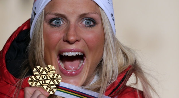 Winner Therese Johaug of Norway celebrates on the podium during the medal ceremony after the women's 10 km Free Individual competition of the Nordic Ski World Championships in Val di Fiemme, Italy, Tuesday, Feb. 26, 2013. (AP Photo/Matthias Schrader)