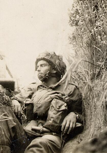 Juno Beach, a weary 1st Canadian Paratrooper takes a rest in a slit trench. Varaville, Normandy. June 6, 1944