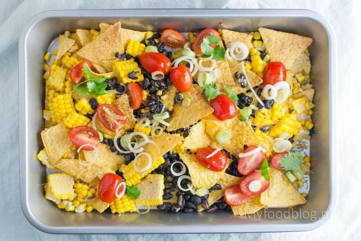 Zwarte bonen, maïs, tortillachips en koriander. Klassieke Mexicaanse ingrediënten in een nacho schotel.