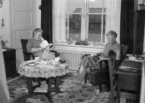 Lezen. Twee oudere vrouwen zitten te lezen bij het raam in een kamer met een rond tafeltje waarop een geborduurd kleed ligt. Nederland, 1 juni 1953.