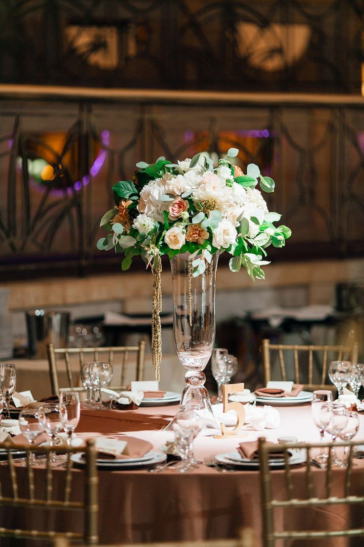 The decor of the guest tables. The high centerpiece  with use using roses, carnations, hydrangeas, methiol, eucalyptus and salal