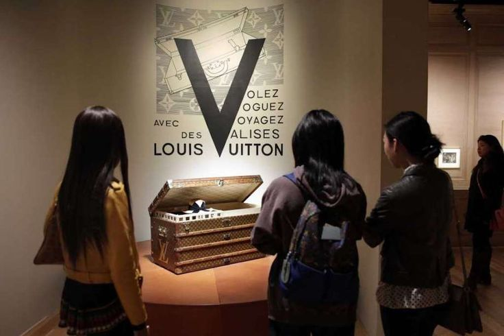 Louis Vuitton Luggage Exhibition Details a History of Modern Travel  Visitors view a 1906 trunk displayed as part of the 'Volez Voguez Voyagez' Louis Vuitton exhibit in the former American Stock Exchange building in New York's Financial District. The luxury French brand founded in the mid-19th century is telling its story with a free museum-like exhibition of artifacts products and immersive displays. Richard Drew / Associated Press  Skift Take: Fashion-minded travelers and history buffs…