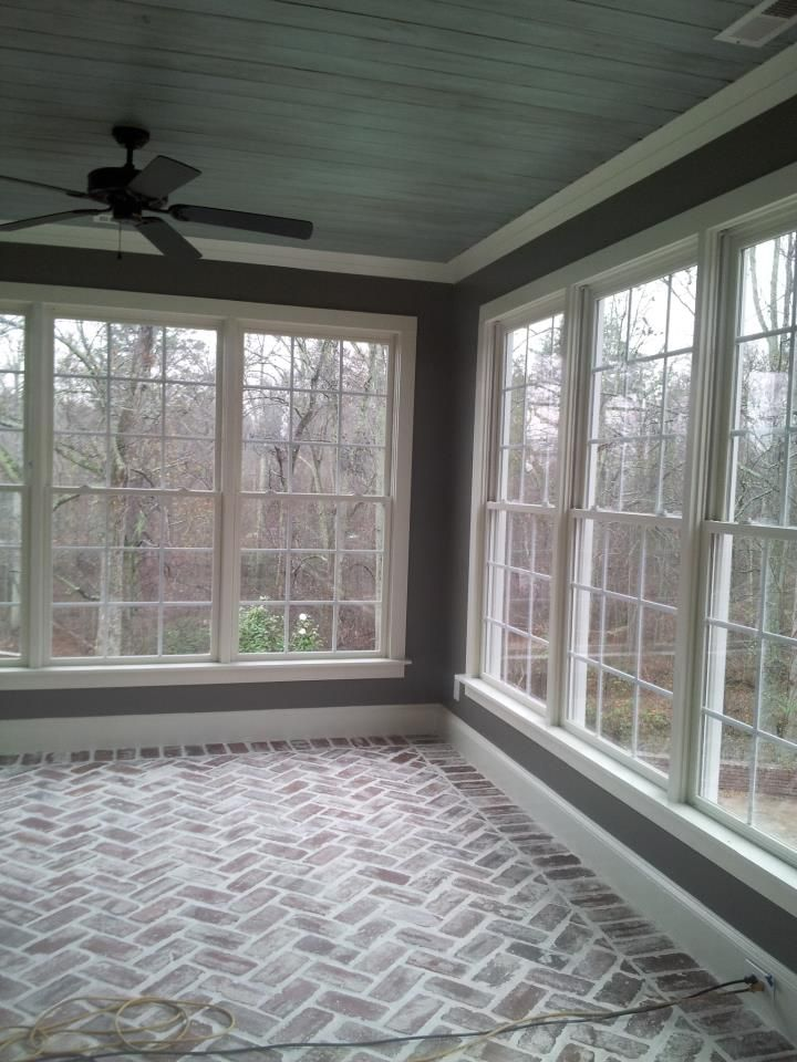 "Sun Room: Reclaimed 100 yr. old brick laid in a herringbone pattern, antiqued ""Haint"" blue ceiling."