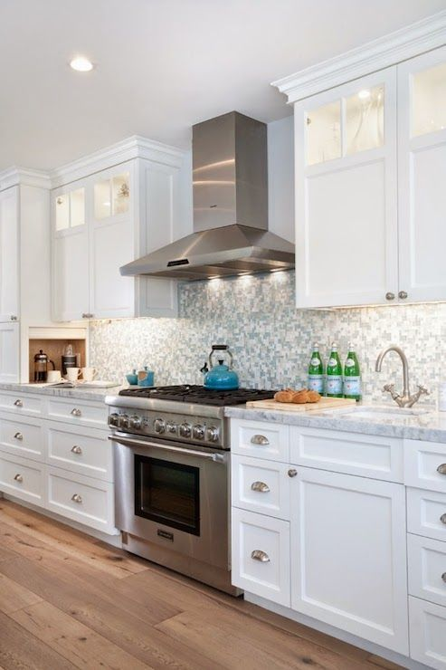 White and blue kitchen features white cabinets adorned with brushed nickel hardware alongside white and gray quartzite counters which frame a stainless steel range and hood situated between a prep sink to the right and a hidden coffee station to the left highlighted by a blue iridescent tile backsplash.: