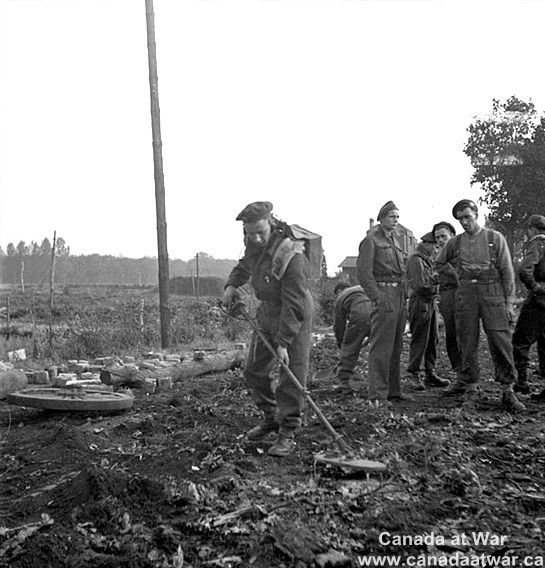 Belgium - Sapper W.H. Lindstrom, 2nd Field Company, Royal Canadian Engineers (R.C.E.), sweeping for mines at a roadblock. October 5, 1944, Cappellen, Belgium.