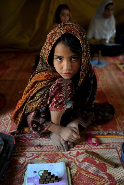 Una niña afgana posa para una foto mientras se asiste a una clase en un campamento en Kabul el 11 de octubre de 2011.  Bajo el régimen talibán, la escuela las niñas habían sido cerradas, las mujeres se les prohibió trabajar fuera del hogar, y también obligación de llevar el burqa.