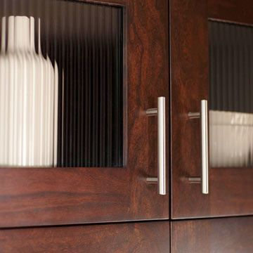Glass-front doors and open shelving prevent the dark cabinetry from overwhelming the small kitchen. Ribbed-glass inserts in selected upper cabinets break up the tall wall of wood while slightly obscuring the cabinets' contents.