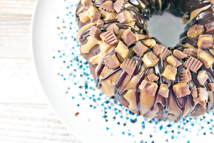 Chocolate Peanut Butter Cup Bundt Cake: dense chocolate cake covered in peanut butter and milk chocolate ganache, topped with chopped Reese's peanut butter cups. Mix by hand in two bowls for an easy, impressive dessert. {Bunsen Burner Bakery}
