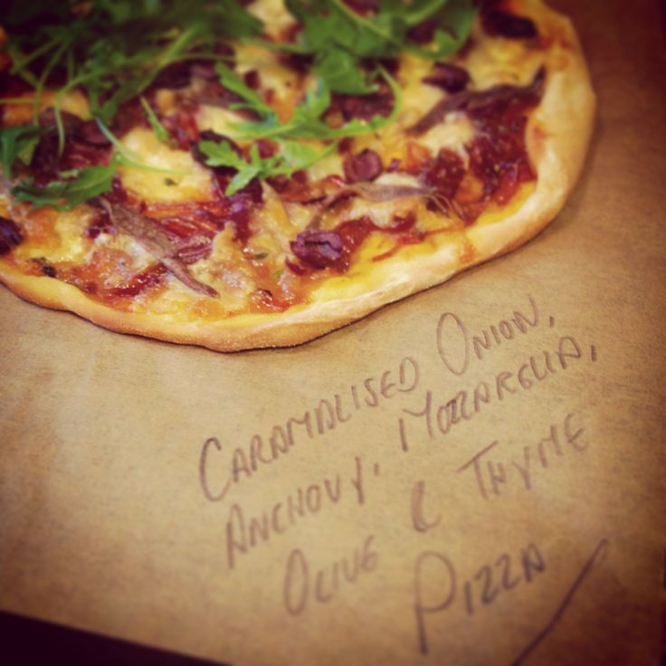 Caramelised red onion, anchovy, mozzarella, olive and thyme pizza.