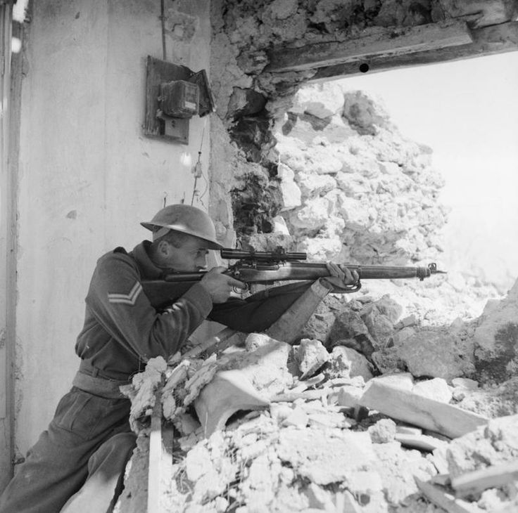 New Zealand corporal sniper posing with his No.4 MkI (T) in the ruins of Cassino, 26 March 1944