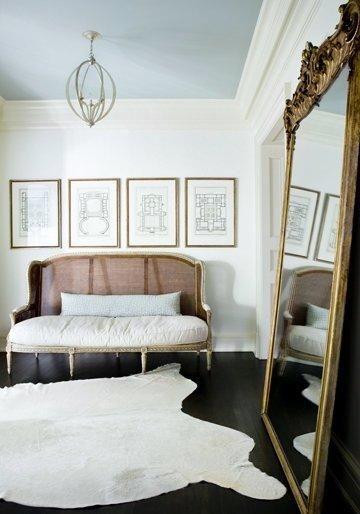 Foyer: blue ceiling, gilt mirror, ivory cowhide, artwork arrangement, settee