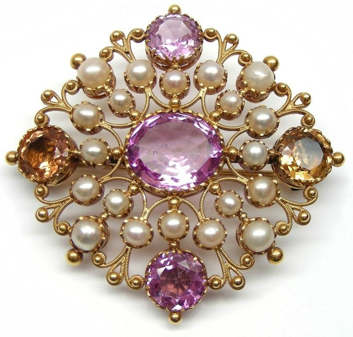Antique gold, pearl and topaz brooch, English c.1825 , of lozenge outline, centred by an oval cut pink topaz with round pink topaz above and below and orange topaz either side, to an openwork bead and scroll gold frame set with pearls