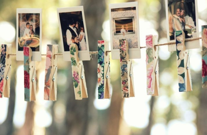 Polaroids clipped with floral clothes pins makes for whimsical & romantic DIY wedding decor.