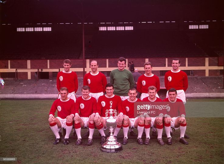 Liverpool team group.... Back Row (from left to right) Willie Stevenson, Ronnie Moran, Tommy Lawrence, Gordon Milne and Gerry Byrne... Front Row (from left to right) Peter Thompson, Alf Arrowsmith, Ron Yeats, Ian St. John, Roger Hunt and Ian Callaghan pose in front of the main stand at Anfield celebrating being crowned the League Division One Champions during a photoshoot held on May 30, 1964 at Anfield, in Liverpool, England. Liverpool were crowned league champions of League Division One…