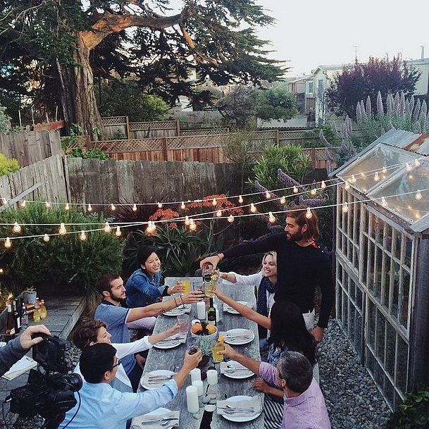 String lights cast the perfect glow over an outdoor picnic style table